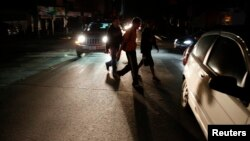 FILE - People walk on a street during a blackout in Caracas, Venezuela, Dec. 2, 2013.