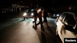 People walk on a street during a blackout in Caracas, Venezuela, Dec. 2, 2013.
