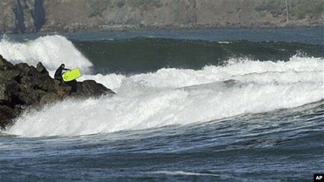 With a tsunami warning in effect for Northern California, a surfer enters the water at Fort Point near the Golden Gate Bridge in San Francisco, California, March 11, 2011