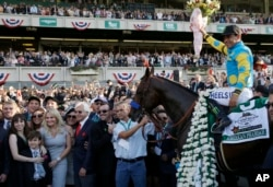 Victor Espinoza sits astride American Pharoah in the winner's circle after gliding to victory in the 147th running of the Belmont Stakes at Belmont Park in Elmont, N.Y., June 6, 2015.