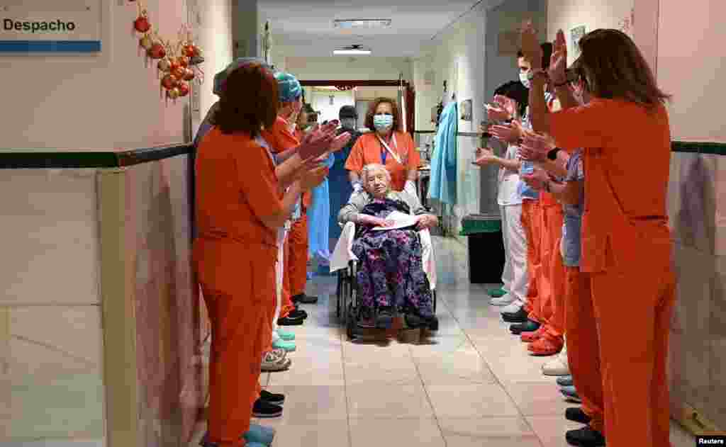 Health workers salute Elena, 104, as she leaves the Gregorio Maranon hospital, after being treated for the COVID-19 in Madrid, Spain. (Hospital Gregorio Maranon/Handout)