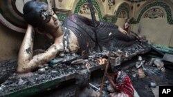 Một Phật tử cầu nguyện trước tượng Phật bị hư hại trong một ngôi chùa ở Ramu, Bangladesh bị những người theo đạo Hồi tấn công, đốt phá
