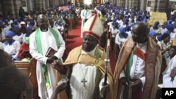 Anglican Bishop Nolbert Kunonga, front center, in church as members of Anglican church supporting him hold placards attacking homosexuality and condemning the visit by Britain's Archbishop of Canterbury Rowan Williams, in Harare, Oct. 9, 2011.