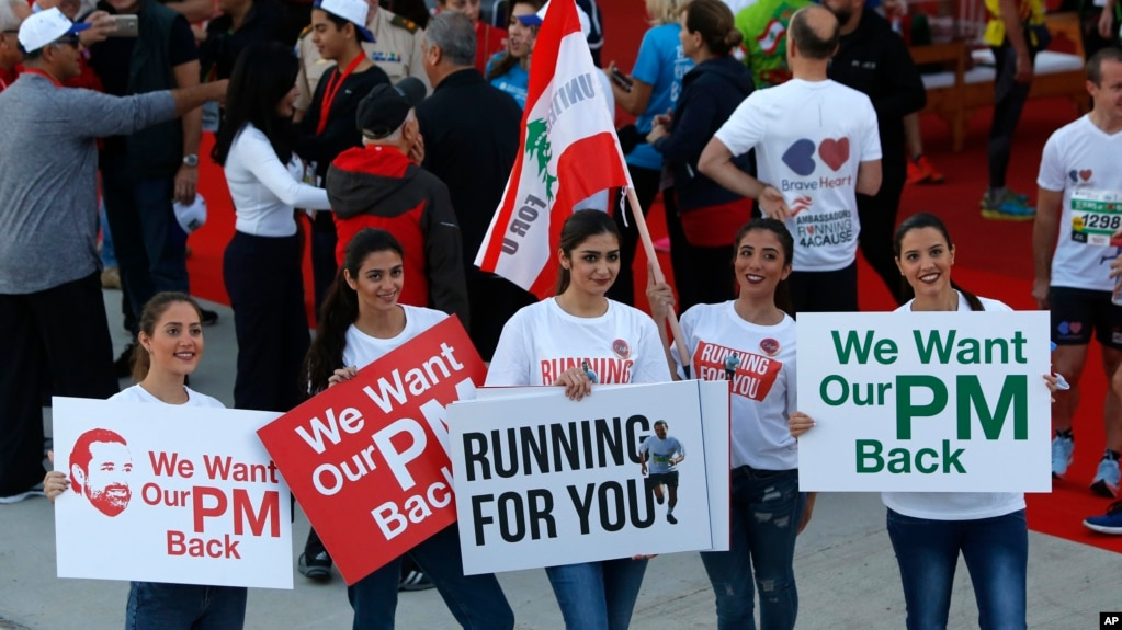 Lebanese women hold placards supporting the outgoing Lebanese Prime Minister Saad Hariri to return from Saudi Arabia during the Beirut Marathon in Beirut, Lebanon, Nov. 12, 2017.