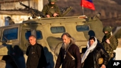 Archbishop Clement of Ukrainian Orthodox Church, center, walks past a pro-Russian armored vehicle, soldiers, Ukrainian military base, Perevalne, March 15, 2014.