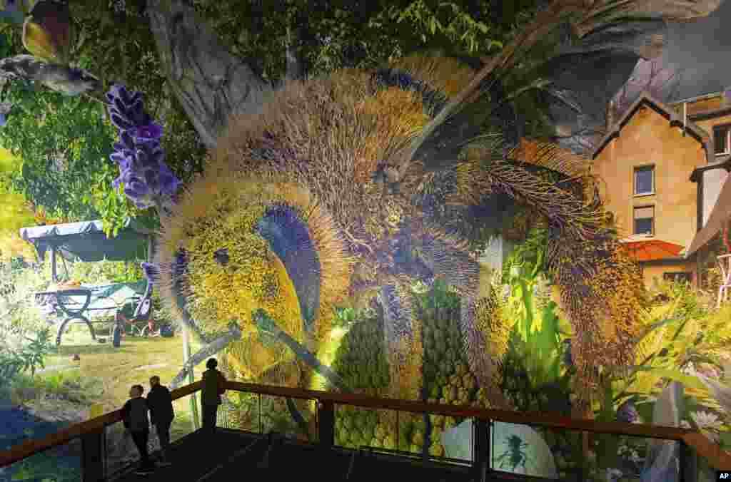 بازدیدکنندگان در مقابل مجموعه عکسهای پانوراما به نام «باغ کارولا، بازگشت به بهشت» اثر «یادگار عزیزی» هنرمند ایرانیتبار در لایپزیگ آلمان