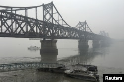 FILE - Trucks move across the bridge linking North Korea with the Chinese border city of Dandong, March 3, 2016. Experts says China is facing a delicate balancing act with sanctions as Pyongyang might use its nuclear and missile capabilities to threaten Beijing.