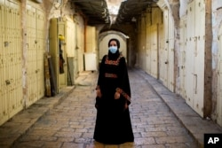 "Israeli Arab Rana Hijazi,19, poses for a portrait wearing her protective face mask in the alleys of Jerusalem's old city, Tuesday, July 21, 2020. Hijazi says ""she advice all people to wear face masks because it is very important for their health."