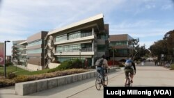 Two students ride bicycles past the Rady School of Management at UC San Diego.