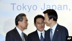 Menlu Jepang, Fumio Kishida, tengah memperhatikan saat Menlu China Wang Yi, kiri, berjabat tangan dengan Menlu Korsel, Yun Byung-se setelah konferensi pers seusainya pertemuan trilateral di Tokyo, hari Rabu, 24 Agustus 2016 (foto: Katsumi Kasahara/Pool Photo via AP)