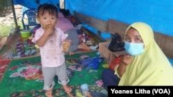 Ibu Rida (baju kuning) saat berada di tenda terpal yang didirikan di depan rumahnya yang rusak berat akibat gempa di desa Kayuangi, Kecamatan Malunda. Jumat (28/1/2021). (Foto: VOA/Yoanes Litha)