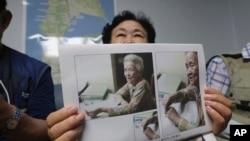 韩国女士申筠顺举着曾境被迫充当日军慰安妇的92岁母亲白奉礼的照片,在首尔的家中接受采访。(2020年7月29日)