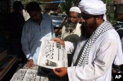 Des Pakistanais lisant des journaux annonçant la mort de Ben Laden
