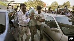 Cảnh sát Ấn Độ mặc thường phục áp giải nghi can (giữa) liên quan đến vụ nổ bom chiếc xe hơi chở viên chức ngoại giao của Israel
