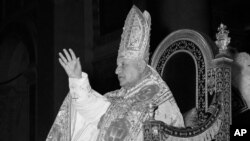 FILE - Pope John XXIII blesses spectators as he is carried on a portable throne to St. Paul's Basilica in Rome, Jan. 25, 1959.