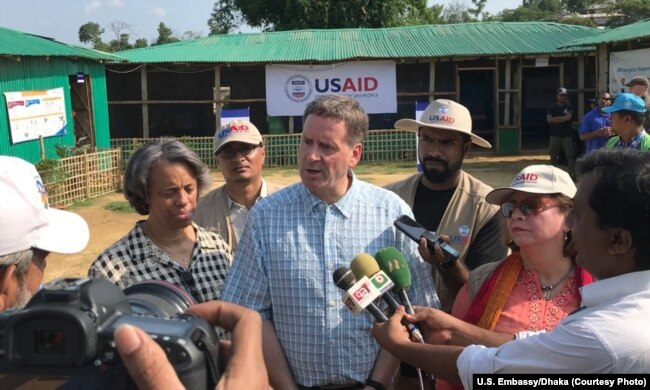 FILE - USAID Administrator Mark Green, center, speaks to reporters at the Balukhali Rohingya refugee camp in Cox's Bazar, Bangladesh, May 15, 2018. He says a new measure promoting U.S. prviate investment in developing countries will aid their economies and 'advance foreign policy interests.'.