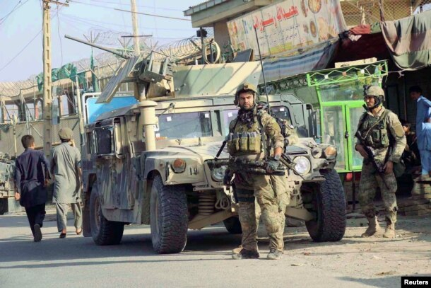 Afghan security forces keep watch in front of their armored vehicle in Kunduz city, Afghanistan, Oct. 4, 2016.