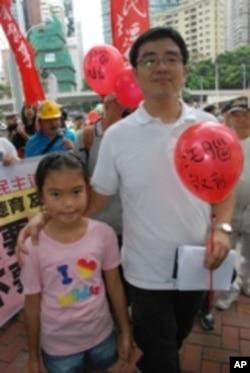 香港市民梁先生(右)手持諷刺國民教育是「染紅洗腦」的汽球,與十歲女兒一同參加遊行