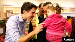 Thủ tướng Canada Justin Trudeau (trái) chào đón người tị nạn Syria đến phi trường Toronto ngày 11/12/2015.