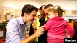 Syrian refugees are greeted by Canada's Prime Minister Justin Trudeau in 2015.