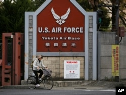 FILE - A woman cycles from the U.S. Air Force's Yokota Air Base in Tokyo's western suburbs, April 27, 2017. Residents living near U.S. military bases in Japan are on the frontline of North Korea's dispute with America, and if Pyongyang were to attack they would have just minutes to shelter from incoming missiles.