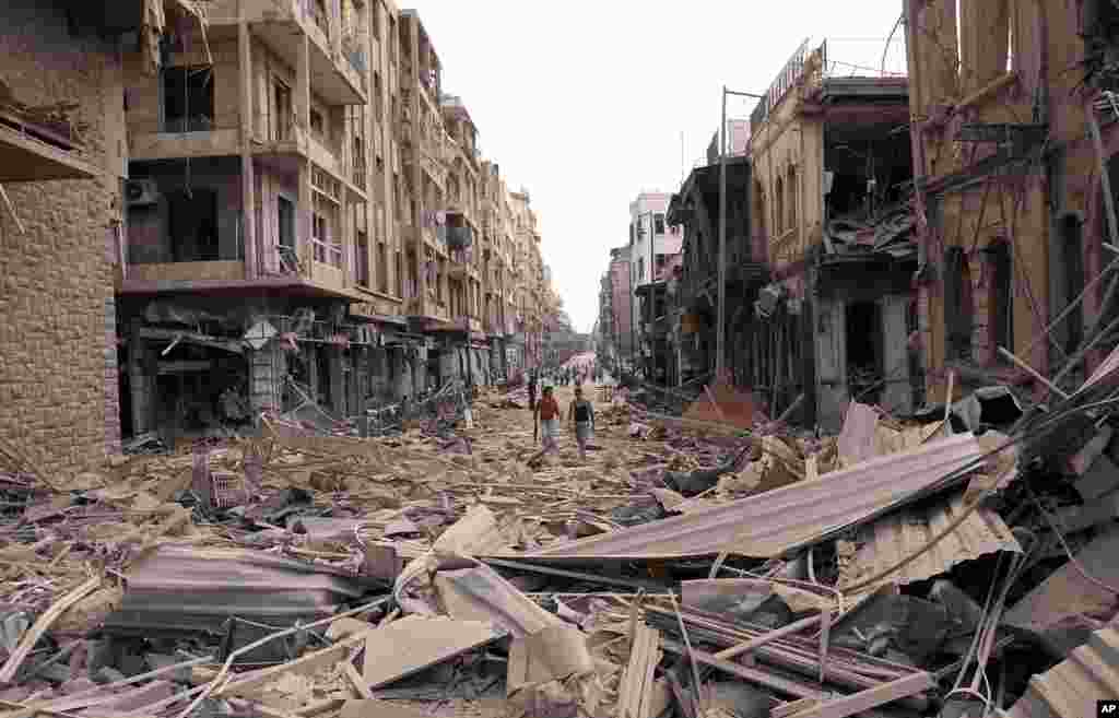 This photo released by the Syrian official news agency SANA shows Syrian men walking between destroyed buildings where bombs exploded in Saadallah al-Jabri square, in Aleppo, Syria, October 3, 2012.