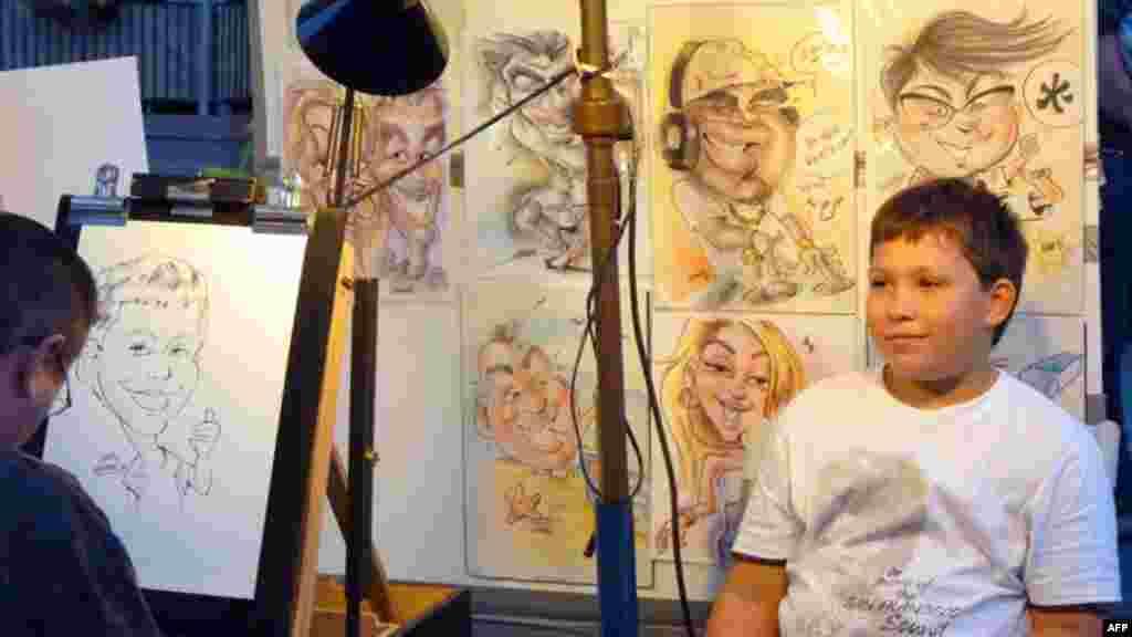 Sanatçılar sokağında karikatürünü çizdiren bir çocuk