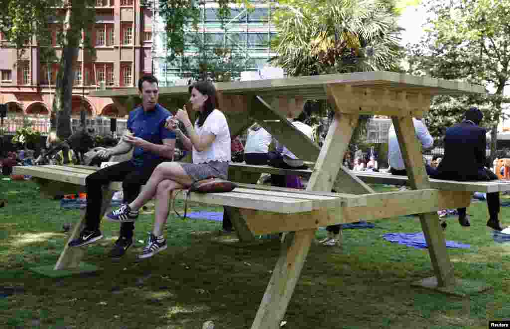 People sit on an oversize picnic table in Soho Square in London.