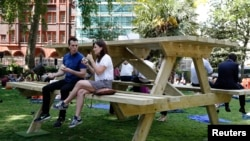 People sit at an oversize picnic table in Soho Square in London May 19, 2014.
