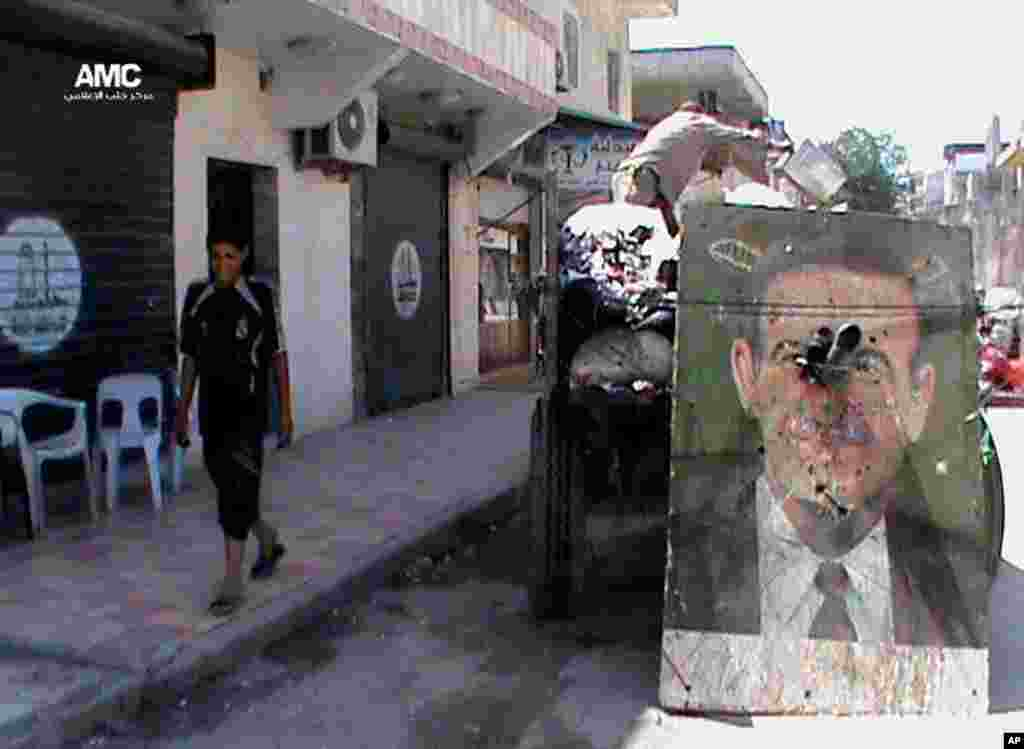 This citizen journalism image provided by Aleppo Media Center AMC shows a poster of late Syrian President Hafez Assad on a garbage truck, in Aleppo, Syria, June 6, 2013.