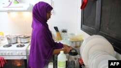 FILE - A refugee from Somalia, who had previously attempted to commit suicide, is seen doing kitchen chores at Camp Five on the Pacific island of Nauru, Sept. 2, 2018.