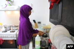 FILE - A refugee from Somalia, who had attempted suicide, is seen doing kitchen chores at Camp Five on the Pacific island of Nauru, Sept. 2, 2018.