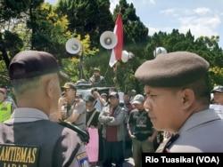 Kelompok massa menolak diskusi buku Ahmadiyah di Bandung, 5 Januari 2019. Mereka berorasi dengan pengawalan ketat kepolisian. (Foto: Rio Tuasikal/VOA)