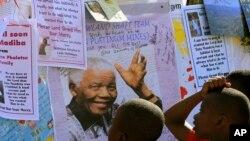 Anak-anak Afrika Selatan membaca pesan-pesan dan doa kesembuhan bagi Nelson Mandela, di luar rumah sakit Pretoria, di mana Mandela dirawat (1/7).