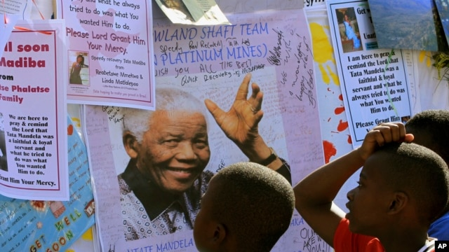 Young boys read  get well messages with a photograph of former South African President Nelson Mandela, outside the Mediclinic Heart Hospital where he is being treated in Pretoria, South Africa, July 1, 2013.
