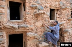 Penjaga lumbung, Mustapha Ait Lamine, memanjat ruang penyimpanan lumbung kuno yang berfungsi sebagai tempat aman untuk menyimpan biji-bijian dan barang berharga, di dekat Desa Lalla Taalat, di wilayah Souss Massa, Maroko, 9 Juni 2021. (REUTERS/Abdelhak Balhak)