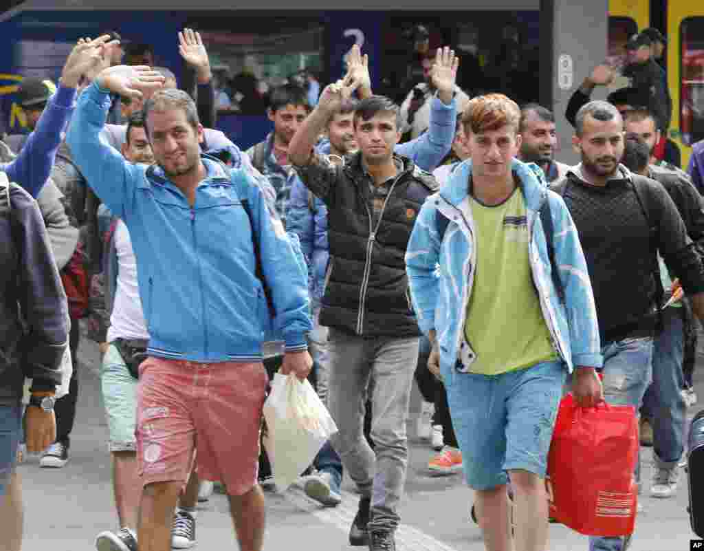 Refugees wave as they arrive at the main train station in Munich, Germany, Saturday, Sept. 5, 2015. Hundreds of refugees arrived in various trains to get first registration as asylum seekers in Germany.