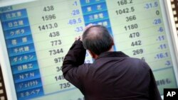 Một người đàn ông nhìn vào bảng chứng khoán điện tử cho thấy chỉ số Nikkei 225 của Nhật Bản ở Yokohama, gần Tokyo, thứ Tư ngày 10/2/2016.