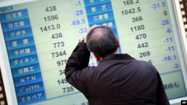 A man scratches his head as he looks at an electronic stock board showing Japan's Nikkei 225 in Yokohama, near Tokyo, Wednesday, Feb. 10, 2016.