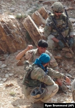 In this undated photo provided by Ryan Brummond, Mohammad Khalid Wardak, center, speaks to a U.S. solider in Afghanistan in Afghanistan