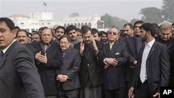Pakistani PM Yousuf Raza Gilani, center, surrounded by officials and members of his government, offers a prayer during the funeral procession of Punjab Gov. Salman Taseer in Lahore, Pakistan, 05 Jan 2011.