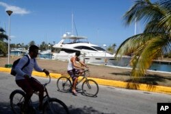 People cycle past U.S. yacht Still Water, moored at Hemingway Marina in Havana, Cuba, Thursday, Aug. 6, 2015.