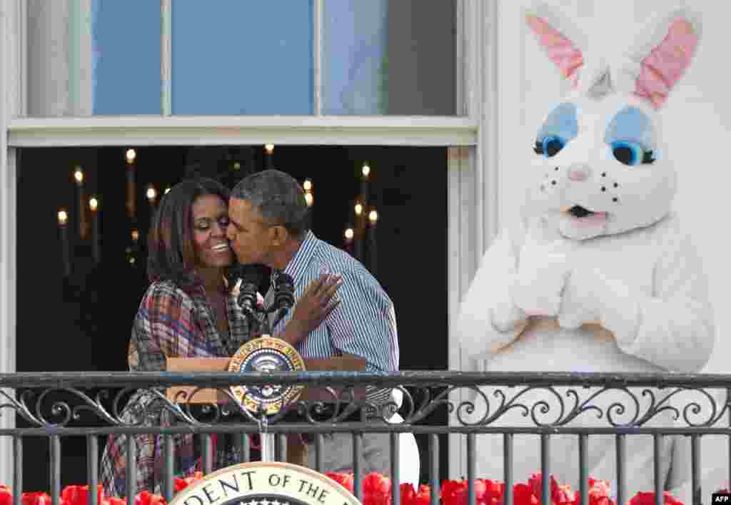U.S. President Barack Obama kisses first lady Michelle Obama alongside the Easter Bunny during the annual White House Easter Egg Roll on the South Lawn of the White House in Washington, D.C.