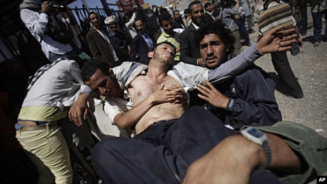 A Yemeni wounded protestor is carried from the site of clashes with security forces in Sanaa, Yemen, October 25, 2011.