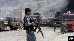 Un agente de policía de Afganistán custodia el área tras el ataque que dejó camiones de la OTAN incendiados en la base Torkham.