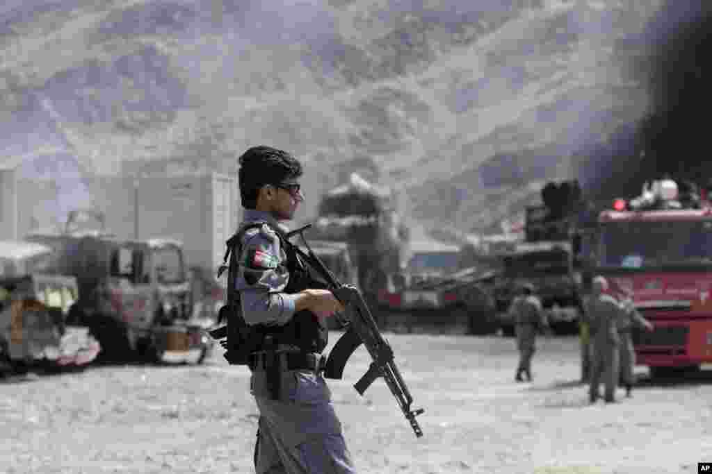 An Afghan police officer stands guard near burning NATO supply trucks following an attack by militants in Torkham, Afghanistan, Sept. 2, 2013.