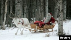 FILE - A man dressed as Santa Claus rides his sleigh, pulled by a reindeer, as he prepares for Christmas on the Arctic Circle in Rovaniemi, northern Finland, Dec. 19, 2007.