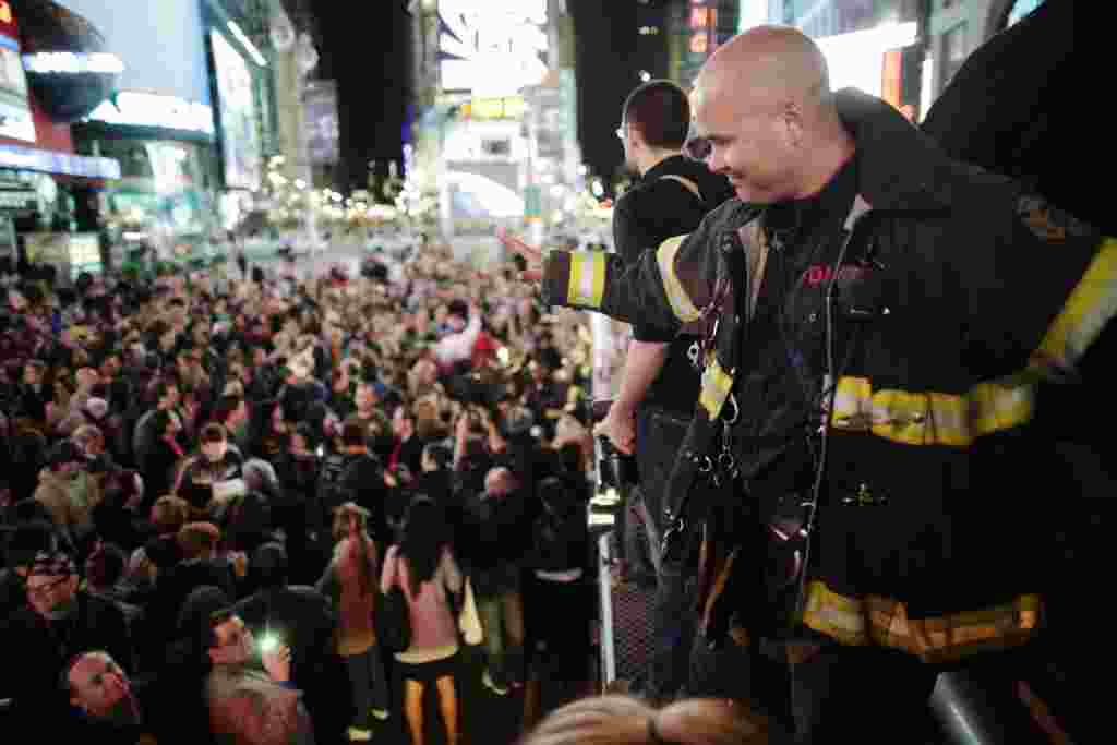 A firefighter waves to the crowd as people celebrate after al-Qaida leader Osama bin Laden was killed in Pakistan, during a spontaneous celebration in New York's Times Square, May 2, 2011. Bin Laden was killed on Sunday in a firefight with U.S. forces in
