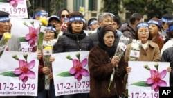Người dân cầm biểu ngữ tại trung tâm Hà Nội để kỷ niệm 37 năm cuộc chiến biên giới Việt-Trung. Các cư dân đã thắp hương và đặt hoa tại tượng đài Lý Thái Tổ trong buổi lễ kéo dài khoảng một giờ đồng hồ.