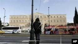A woman stands opposite the Parliament in central Athens, Tuesday, Nov. 27, 2012.